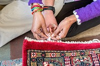 Jaipur, India - Hands weaving threads on oriental rug.
