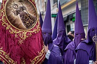 Nazarenos participating in a religious procession, with the traditional robes and hoods and carrying a banner for their brotherhood during Semana Sant...