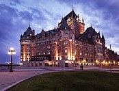 Fairmont Le Château Frontenac lit by street lights at dusk, luxury grand hotel Chateau Frontenac, National Historic Site of Canada. Old Quebec City, Q...