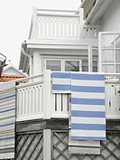 Stripy woven mats hanging out to dry after the rain on the wooden balcony of a harbour side house near Gothenburg, Sweden.