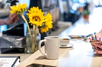 Partial view of fingers on a mobile phone in a coffee shop with a bouquet of sunflowers and a coffee cup.