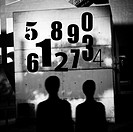 Numbers on a wall. Silhouettes of people.