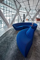 A 4 year old caucasian boy relaxes on a huge blue sofa in the reception lobby of the Hyatt Capital Gate 5 star hotel, designed by the architects RMJM ...