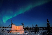 Nightsky and trappers tent lit up with aurora borealis, northern lights, wapusk national park, Manitoba, Canada.