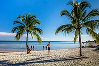 Palm trees and people on sandy Smathers Beach on the Atlantic Ocean in Key West Florida on a blue sky summer day.