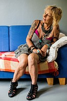 Tilburg, Netherlands. Mature adult caucasian woman, portrait, while sitting on a living room sofa.