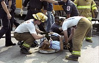 Firefighters work on a woman injured in a car accident in Glendale, Md