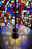 Abstract colors in a stained glass window mosaic at a baptismal font with cross in a Toronto Roman Catholic church.