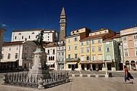 Tartini Statue in Tartini Square Piran Slovenia with St. George's Parish Roman Catholic Church and clock and bell tower.