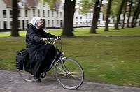 Bruge, nun ride a bicycle. The Beguinage of Bruges was founded in 1245 by the Countess of Flanders, Margaretha of Constantinopel, daughter of Count Ba...