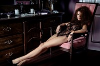 Artistic sensual boudoir portrait of a sexy beautiful woman sitting in a chair by a dresser in underwear with a piercing glaring look and stretched lo...