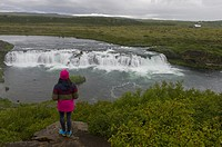 Woman looking at waterfall Faxi (or Faxafoss) in the river Tungufljot in South region of Iceland is part of the golden circle road trip.
