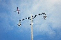 Commercial airliner taking off from San Diego International Airport with lamp post and blue sky in the background