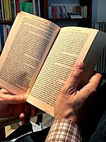 Man's hands holding an open book.