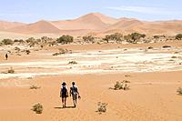 A young couple walking on the desert.
