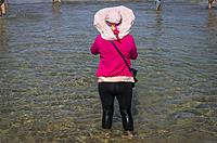 Woman with wet trousers standing in water, Bondi beach, Sydney, NSW, Australia.