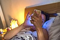 EWoman on her smart phone in bed.