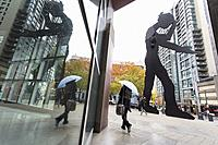 Seattle, Washington: Woman walks by the Hammering Man at the Seattle Art Museum as the first storm of the season lashes the city with high winds and r...