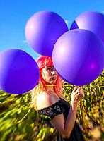 A 25 year old woman with pink hair, looking at the camera in a field of sunflowers holding balloons, Alabama USA.