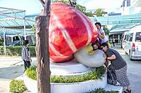 Tourists taking a big bite on a mock cashew at factory outlet in Hatyai, Thailand.