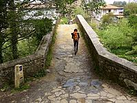 Entering Melide, Coruña. A pilgrim crosses the medieval bridge of San Xoán over the river Furelos, one of the jewels of the civil architecture of the ...
