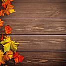 Abstract autumnal backgrounds. Fall maple leaves over vintage wooden desk.