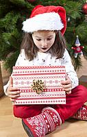 Little girl opening her present under Christmas tree. She is very, very happy.