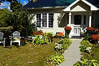 Colorful Fall front garden with green bicycle in Wellington, Prince Edward County Ontario Canada.