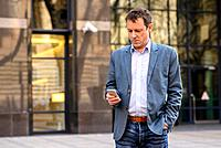 A middle age businessman standing in front of an office building while using his smartphone.