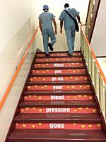 Two medical personnel walk up a set of stairs which show health messages in a hospital, Ontario, Canada.