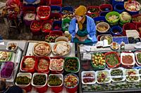 A Woman Sells Pickled Vegetables From A Stall In The Chorsu Bazaar, Tashkent, Uzbekistan.