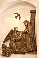 Depiction of the Annunciation of Archangel Gabriel to Mary with descending dove Holy Spirit to conceive Jesus in bronze relief on marble wall Vaughn O...