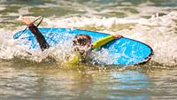 Young boy falls off his surfboard during a surfing lesson. Cape Town, South Africa.