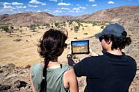 Couple taking picture with tablet in Damaraland - Huab Under Canvas, Damaraland, Namibia, Africa.
