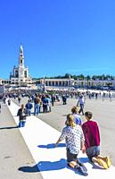 Kneeling Believers Pilgrims 100th Anniversary of Apparations Celebration Basilica of Lady of Rosary Bell Tower Fatima Portugal. Church created on site...
