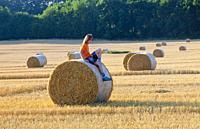 Boy Sitting on a Bale of Hay in Summer.