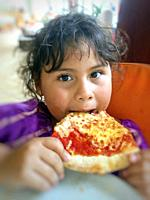 Little girl eating a pizza.