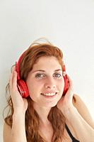 Portrait of young redhead woman with headphones