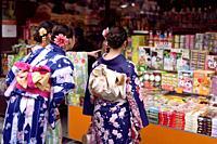 Japanese girls in bright Yukatas stopped by a souvenir store with traditional Kyoto treats and desserts on Matsubara dori street near Kiyomizu-dera. H...