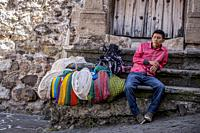 A vendor sells souvenirs for tourists in front of a colonial home in Taxco de Alarcon, Guerrero State, Mexico.