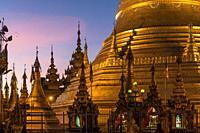 stupas of the buddhist Shwemokhtaw Pagoda at dusk, Pathein, Myanmar, Asia.