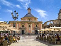 People sitting in outdoor cafes in the Plaza de la Virgen opposite the Basilica Virgin de los Desamparados (centre) and the Cathedral, Cuitat Vella, V...