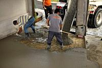 Work crew pouring cement from a cement truck shute over wire mesh on a residential garage floor and spreading with trowel and rake Toronto Ontario Can...