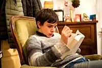 teenager reads a book on the armchair at home.