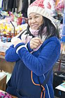 Smiling Thai woman at the morning market in Mae Hong Son. She wears a knitted bonnet and warm coat to ward off the morning chill in this hill country ...