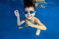 4 years boy in swimming goggles play under water in the pool.