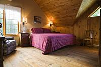 King size bed and antique wooden sitting chair in master bedroom on the upstairs floor inside a cottage style log home, Quebec, Canada. This image is ...