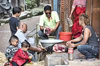 Family cleaning a slaughtered goat for the celebration of the Dasain holiday, Bhaktapur, Nepal.