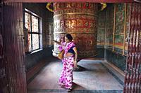 Woman praying at giant prayer wheel, Boudhanath, Kathmandu, Nepal.
