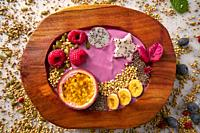 Acai bowl smoothie with passion fruit maracuya seeds banana and raspberries.